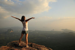Cheering woman hiker open arms at mountain peak. Cliff Royalty Free Stock Photos