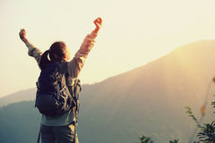 Cheering woman hiker open arms at mountain peak Royalty Free Stock Image