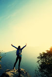Cheering woman hiker open arms at mountain peak Stock Photo