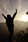 Cheering woman hiker open arms at mountain peak Royalty Free Stock Images