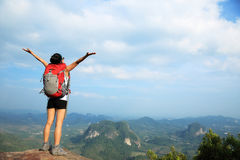 Cheering woman hiker open arms at mountain peak Stock Images