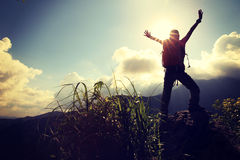 Cheering woman hiker open arms at mountain peak. Cliff Royalty Free Stock Photography