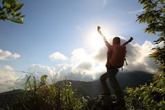 Cheering woman hiker open arms at mountain peak Stock Photography
