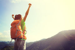 Cheering woman hiker open arms at mountain peak Stock Photos