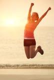 Cheering woman jumping at beach Stock Photos
