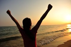Cheering woman open arms on beach Stock Photo