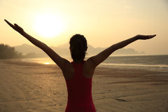 Cheering woman open arms on beach Stock Images