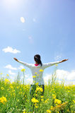 Cheering woman open arms at cole flower field. Under blue sky Stock Photos