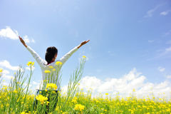 Cheering woman open arms at cole flower field. Under blue sky royalty free stock photography