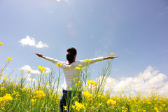 Cheering woman open arms at cole flower field Stock Photos