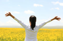 Cheering woman open arms at cole flower field Royalty Free Stock Photo