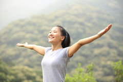 Cheering woman open arms mountain peak Royalty Free Stock Image
