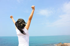Cheering woman open arms at seaside rock Stock Image