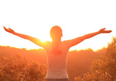 Cheering woman open arms at sunrise mountain peak Royalty Free Stock Image