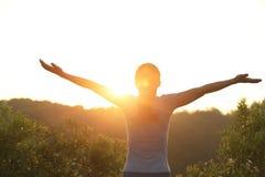 Cheering woman open arms at sunrise mountain peak Stock Photos