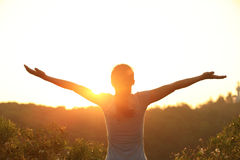 Cheering woman open arms at sunrise mountain peak Royalty Free Stock Photos