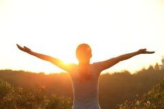 Cheering woman open arms at sunrise mountain peak royalty free stock photos