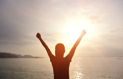 Cheering woman open arms to sunrise at sea Royalty Free Stock Photo