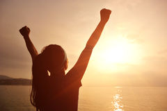 Cheering woman open arms to sunrise at sea Royalty Free Stock Photos
