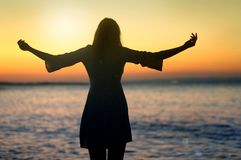 Cheering woman open arms to sunrise at sea. Cheering young woman open arms to sunrise at sea Stock Photos