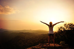 Cheering woman open arms on top hill stock images