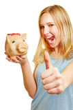 Cheering woman with piggy bank holding thumbs up Stock Photography