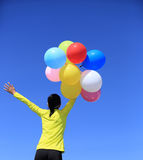 Cheering woman running with colorful balloons on mountain peak Stock Image