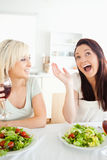 Cheering women drinking wine. In a kitchen Stock Images