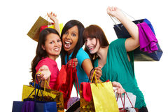 Cheering women with shopping bags. Three happy young women with many colorful shopping bags royalty free stock image