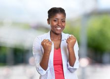 Cheering young african american woman with casual clothes. Outdoors Stock Photos