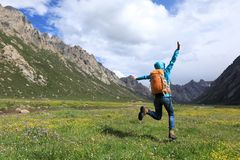 Backpacking woman jumping on flowers and grass Royalty Free Stock Photo