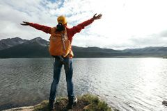 Young backpacking woman open arms on high altitude lakeside. Cheering young backpacking woman open arms on high altitude lakeside Stock Photo
