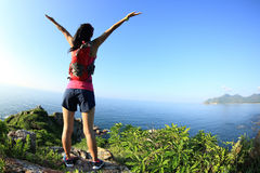 Cheering young fitness woman open arms on seaside mountain Royalty Free Stock Images