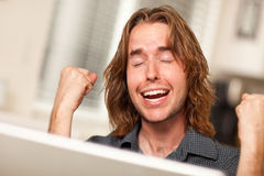 Cheering Young Man Using Laptop Computer Stock Photos