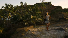 Cheering young woman backpacker at sunrise seaside mountain peak stock video footage
