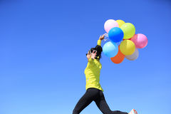 Cheering young woman with colorful balloons Royalty Free Stock Image