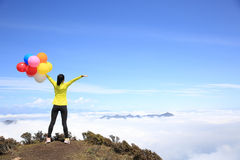 Cheering young woman with colorful balloons on mountain peak Stock Photos