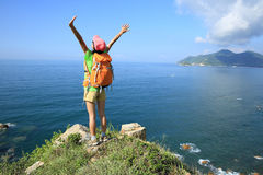 Cheering young woman hiker open arms on seaside mountain Stock Photography