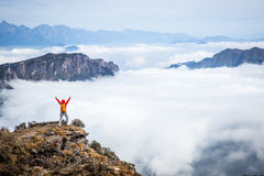 Cheering young woman hiker open arms to beautiful snow mountain Royalty Free Stock Photography