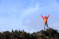 Cheering young woman hiker open arms to beautiful snow mountain Stock Images