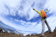 Cheering young woman hiker open arms to beautiful snow mountain Stock Photo