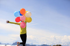 Cheering young woman open arms with balloons Royalty Free Stock Photo