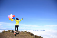 Cheering young woman open arms with balloons Royalty Free Stock Image
