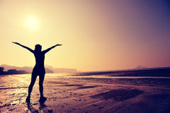 Cheering young woman open arms Stock Images