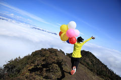 Cheering young woman run with colorful balloons Royalty Free Stock Images