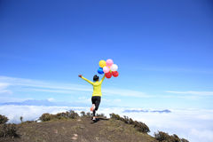 Cheering young woman run with colorful balloons Stock Photos