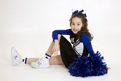 Nine year old Caucasian girl dressed in a blue cheerleader outfit  Royalty Free Stock Photography