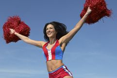 Cheerleader Cheering With Arms Raised While Holding Pompom. Happy cheerleader cheering with arms raised while holding pompom against clear sky Royalty Free Stock Images
