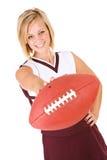 Cheerleader: De vrouw houdt Voetbal aan Camera stand stock afbeeldingen