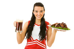 Cheerleader: Girl Holding Ribs and Beer. Cute female as an American sports cheerleader, in red and white outfit.  Isolated on white background Royalty Free Stock Photography